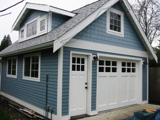 Custom Swinging Garage Doors for a carriage door garage.  Made with a corresponding entry door.  Note the symetrical alignment of all craftsman style door elements.