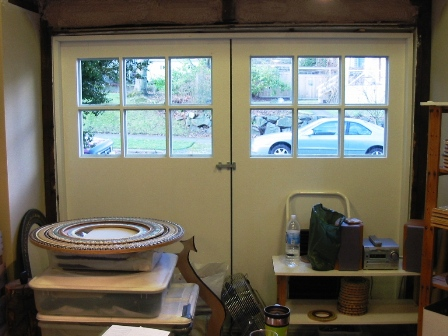 OUTSIDE styling is: Three Flat  Panel/Square Edge/Insulated/Three  Lite/Flush Back.  INSIDE styling  is: Flush Back/Fully Insulated.  The back of the insulated door is  a beautiful FLUSH finish and DOES  NOT EXTEND OR PROTRUDE out from  the surface of the door. Many  other outside and inside styling  choices are available including:  Flat Panel, Raised Panel, Square  Edges, and Profiled Edges for both  insulated and uninsulated real  carriage doors.