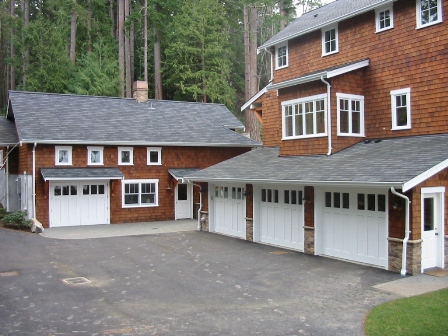 Four custom garage doors.  A Swing Carriage Door, or hinged carraige door, for the real carriage door garage on the left.  Three custom carriage style garage doors for the vintage garage on the right.