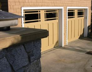 Waterfront custom garage doors in a nine light styling.  Opening as a traditional garage door by rising in sections, the door could also be made to open as a swing-out carriage door for these craftsman style doors.